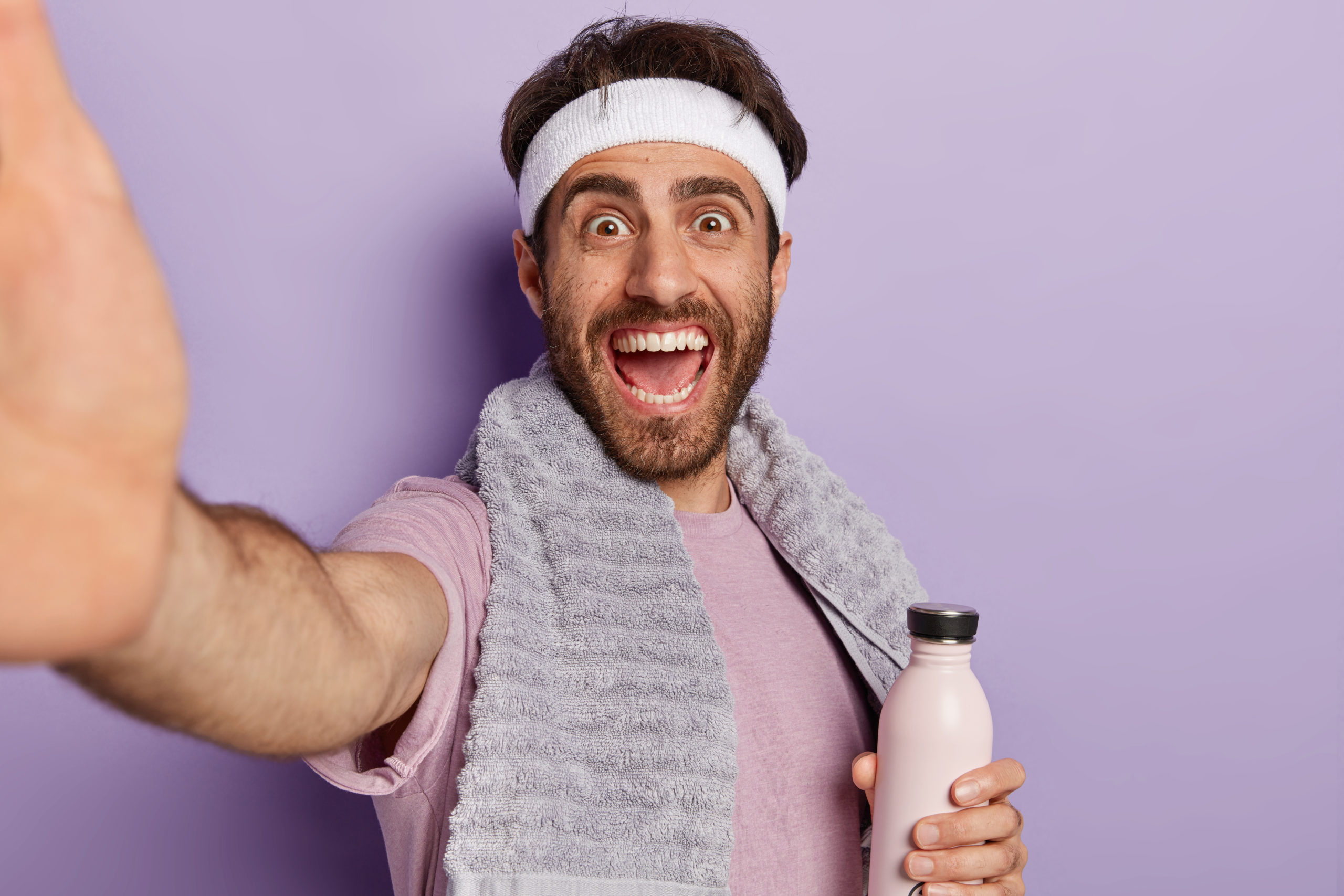 Happy sportsman extends hand with unrecognizable device, takes selfie in gym during workout, holds water bottle, stays hydrated and healthy, being energetic wears towel on neck isolated on purple wall