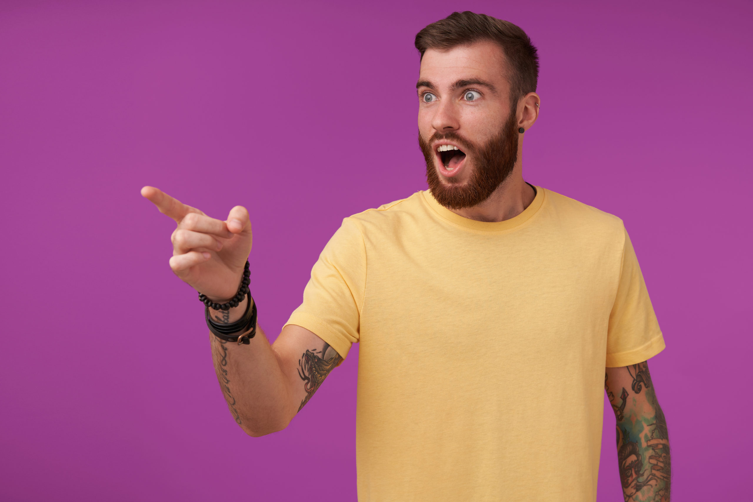 Shocked handsome brunette bearded guy with tattooes wearing yellow t-shirt and fitness watch noticing something and showing on it with forefinger, isolated over purple background